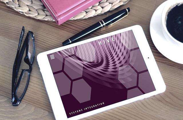 Tablet, okuliare, pero a šálka s kávou položené na stole.jpg