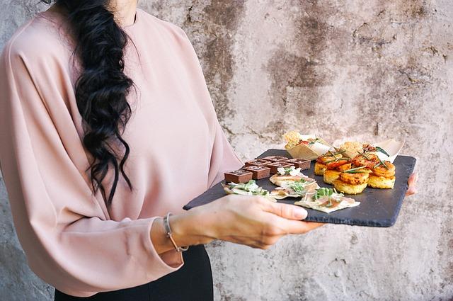 Žena v ružovej blúzke nesie jedlo na kamennom podnose a má na zápästí strieborný náramok.jpg