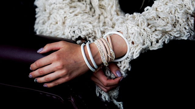 Žena v bielom svetri má na rukách veľa rôznych náramkov.jpg