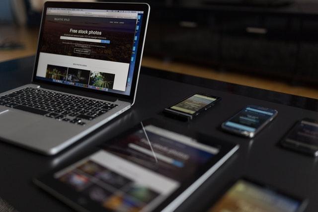 Notebook, telefóny a tablet položené na čiernom stole.jpg